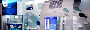 Large exhibition stand with lightbox, freezers for products and seating areas