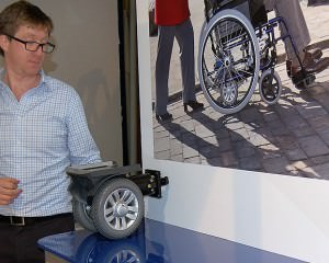 Person demonstrating wheelchair product on a stand