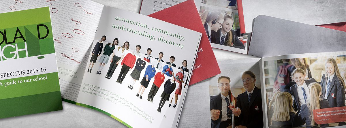 A variety of prospectus booklets open and arranged on surface