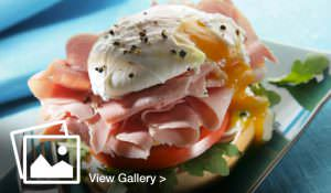 Ham and poached egg bagel with lettuce and tomato